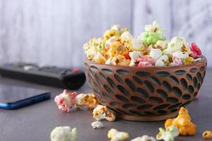 Popcorn in a bowl on wooden table photo