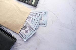 top view of cash and coins in a envelope on table photo