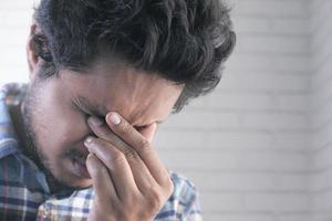 hombre que sufre de dolor de cabeza foto