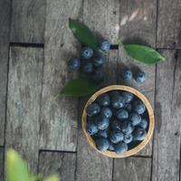 Fresh plums in a wooden bowl on old wooden background