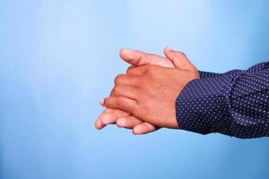 Frotarse las manos sobre fondo azul. foto