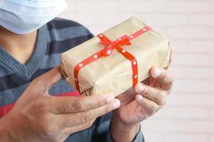 hombre vestido con máscara sosteniendo una caja de regalo foto