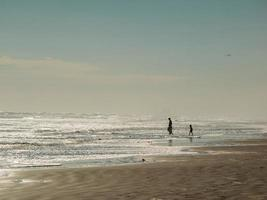 Silhouettes of adult and two children on a beach with cloudy blue sky