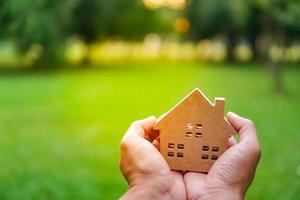 Mano sosteniendo una casa modelo sobre fondo verde de la naturaleza foto