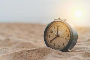 primer plano, de, un, reloj, en la arena, con, luz del sol, plano de fondo foto