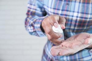 Hombre usando gel desinfectante para prevenir virus foto