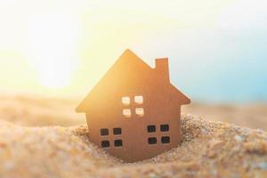 primer plano, de, pequeño, casa, modelo, en, la arena, con, luz del sol, plano de fondo foto