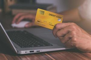 Person using a credit card to shop online through computer photo