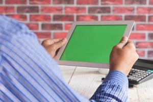 Man using a digital tablet at a desk photo