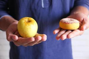 manzana y donut en mano foto
