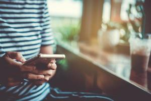 Mujer usando un teléfono inteligente en la cafetería con luz solar foto