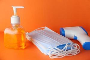 Mascarillas y desinfectante de manos sobre fondo naranja