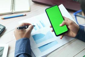 hombre usando un teléfono inteligente en un escritorio foto
