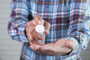 hombre usando desinfectante de manos foto