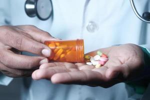 la mano del médico que sostiene el envase de la píldora
