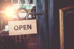 Open sign hanging on door of business shop
