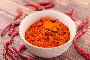 Chili powder and dried peppers on table background photo