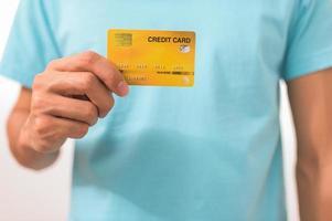 hombre sosteniendo una tarjeta de crédito