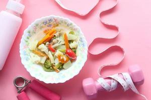 Concepto de fitness con mancuernas, verduras frescas y cinta métrica sobre fondo rosa foto