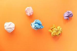 Colorful crumpled paper on orange background photo