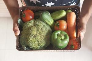 sosteniendo una canasta de verduras