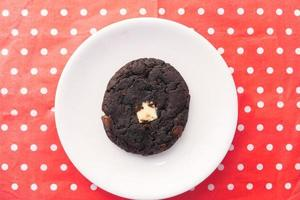 Chocolate cookie on red polka dot background photo
