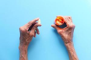 Mujer tomando pastillas sobre fondo azul. foto