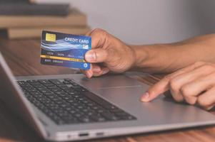 People use credit cards to shop online through computers photo