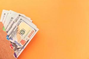 Close up of 100 dollar cash on orange background photo