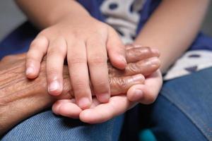 mano de niño sosteniendo la mano de una mujer mayor foto