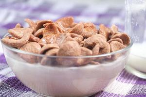 Corn flakes and milk on table photo
