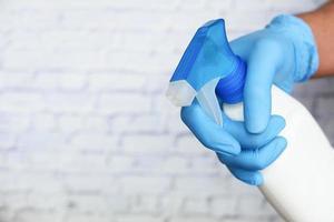 Mano en guantes de goma azul sosteniendo una botella de spray