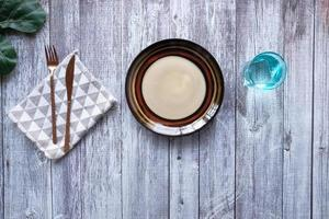 Empty plate with a knife and fork on wooden background photo