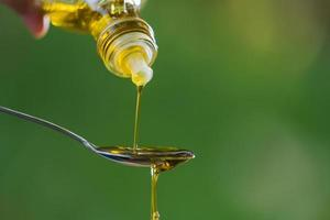 Pouring olive oil into spoon on green park garden background photo