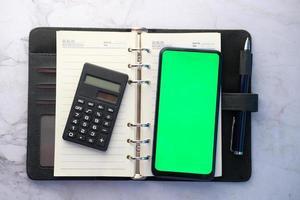 vista superior del teléfono inteligente en una libreta de direcciones foto