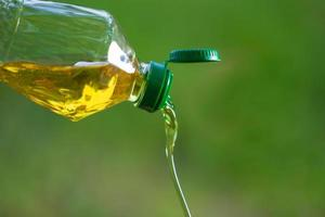 Vegetable oil pouring from bottle with nature background photo