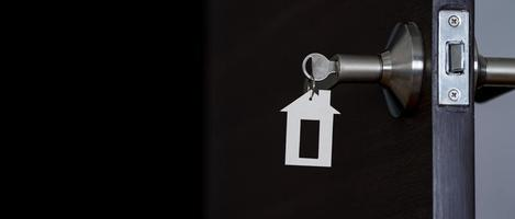 Open door at home with key in keyhole, new housing concept