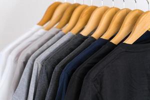 Cerca de camisetas en perchas, antecedentes de prendas de vestir foto