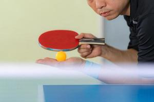 Macho jugando tenis de mesa con raqueta y pelota en un pabellón deportivo foto