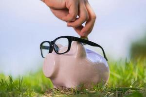 Pink piggy bank with glasses on grass and hand putting in a coin photo