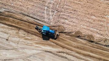Vista superior de los vehículos tractores agrícolas que trabajan en el campo foto