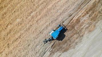 Vista superior de los vehículos tractores agrícolas que trabajan en el campo