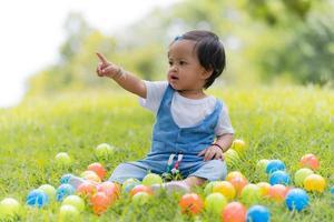 niño pequeño feliz y bolas de colores en el parque foto