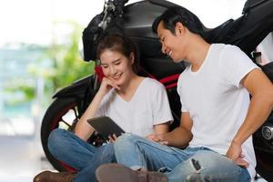 Happy couple using digital tablet at home with a motorcycle background photo