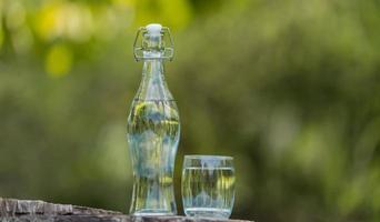 Botella de agua potable y vaso con fondo natural.