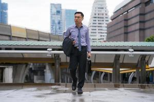 Asian businessman walking and holding briefcase with business office buildings in the city background