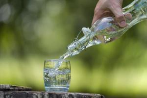 Mano vertiendo agua potable de botella en vaso con fondo natural foto
