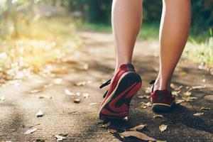 Woman wearing running shoes and running on nature green background