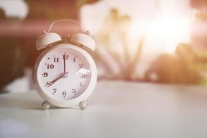 Selective focus of alarm clock showing 8 o'clock on table with nature bokeh background