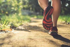 Woman wearing running shoes and running on nature green background photo